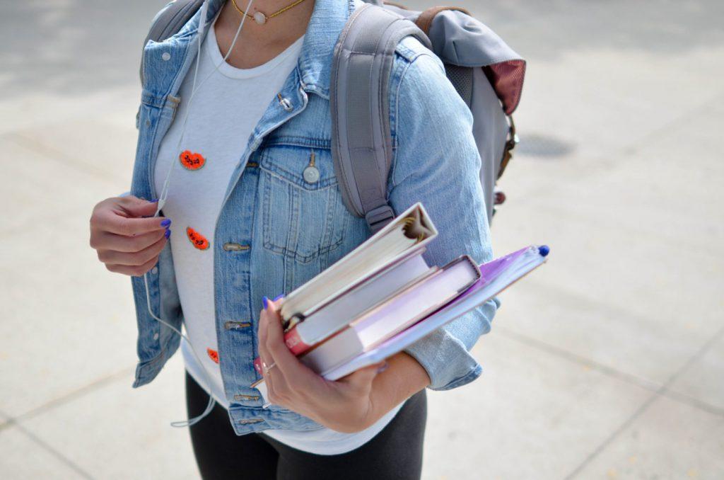 Alunno con libri che va a scuola